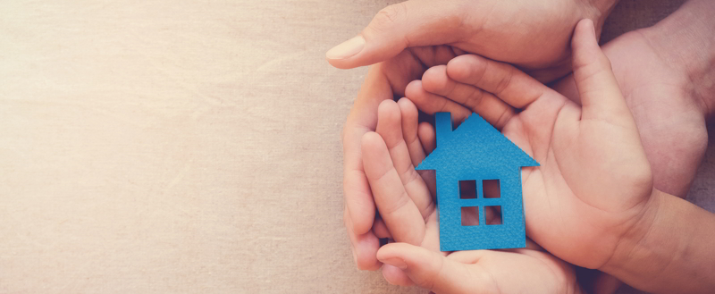 Adult and child hands holding blue paper house for asset protection and inheritance concept.