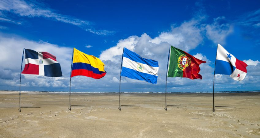 the flags of panama, colombia, nicaragua, portugal and dominican republic flapping in the wind on a beach