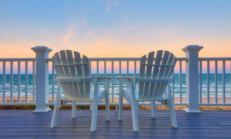 Chair sits on the balcony deck of a house looking out over the beach and the ocean