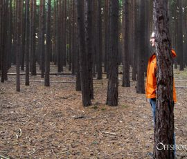 Man in Bright Orange Jacket Hiding Behind A Tree