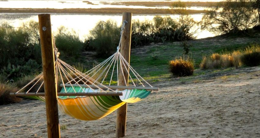 A striped hammock in the shade overlooks the ocean