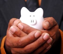 Man holding small piggy bank in his hands
