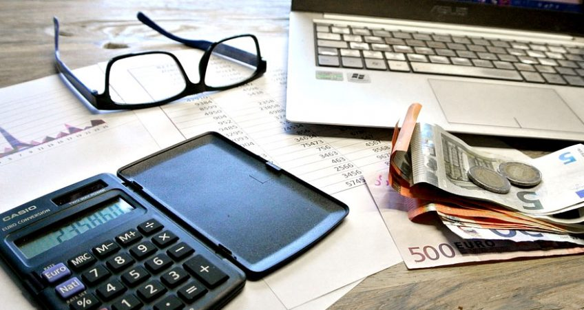 A desk with laptop, glasses, calculator, and euros