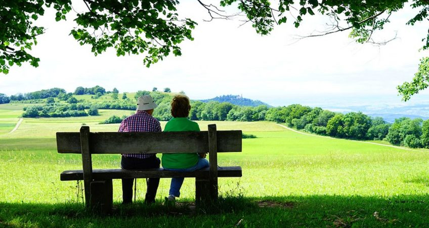 A senior couple sitting in a bench in a park