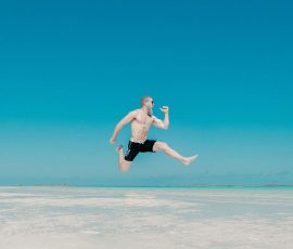 a man in a bathing suit jumping very high against a blue background
