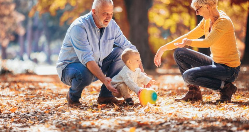Grandparents playing outside with their grandchild