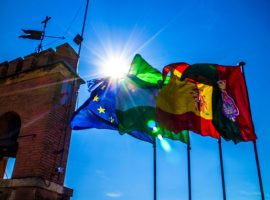 EU, Portugal and Spanish Flag flying with blue sky and sun in the background