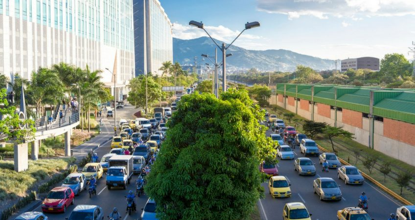 The cityscape of El Poblado, Medellin, Colombia, with traffic spanning 6 lanes divided by trees in the middle and mountains off in the distance.