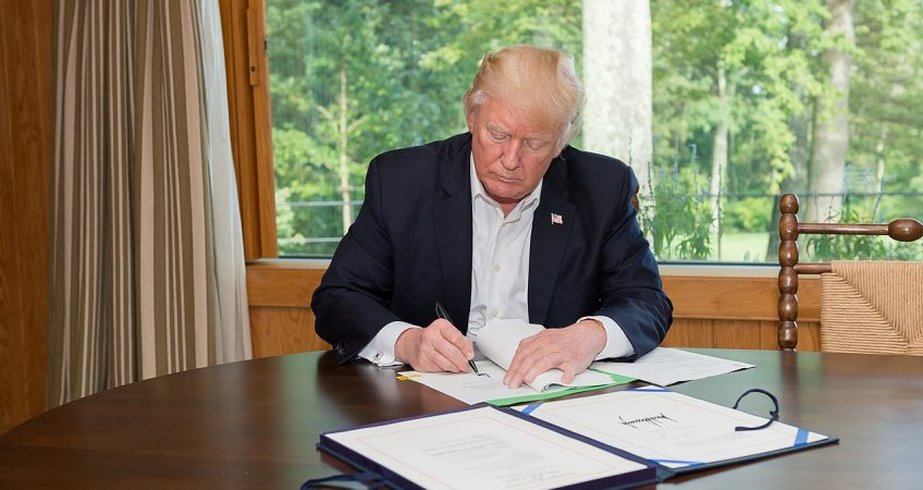 Donald Trump Signing A Bill In Front Of A Window. The View Outside Is Of Green Trees, Trump Is Sitting At A Wooden Table And Not Wearing A Tie