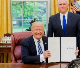 The Donald Posing with a bill which he has recently signed in the white house