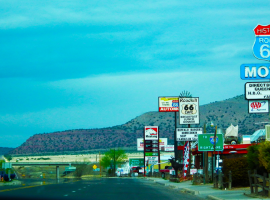 Image of a town on route 66. Neon signs in the foreground and mountains in the background