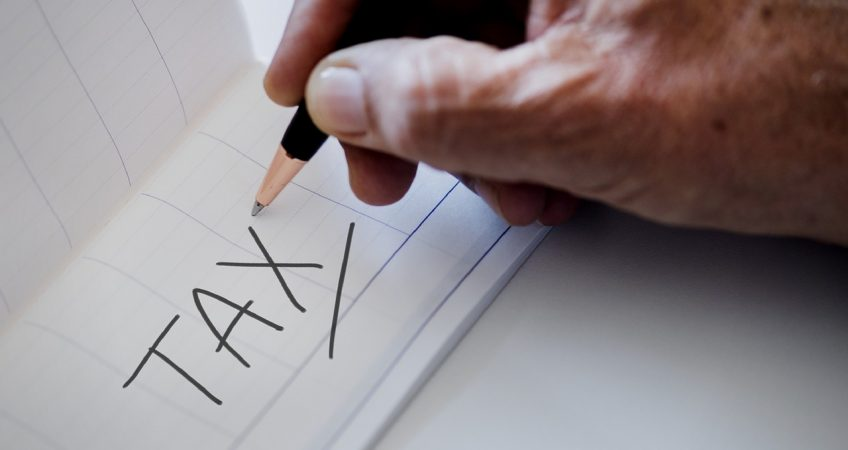 hand holding a pencil which has written the word tax in capital letters on a piece of paper