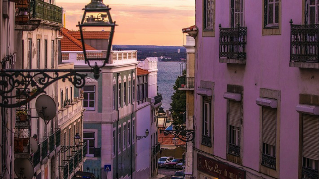 lisbon at sunset. view of colonial buildings on either side of the street down to the river at the bottom of the hill