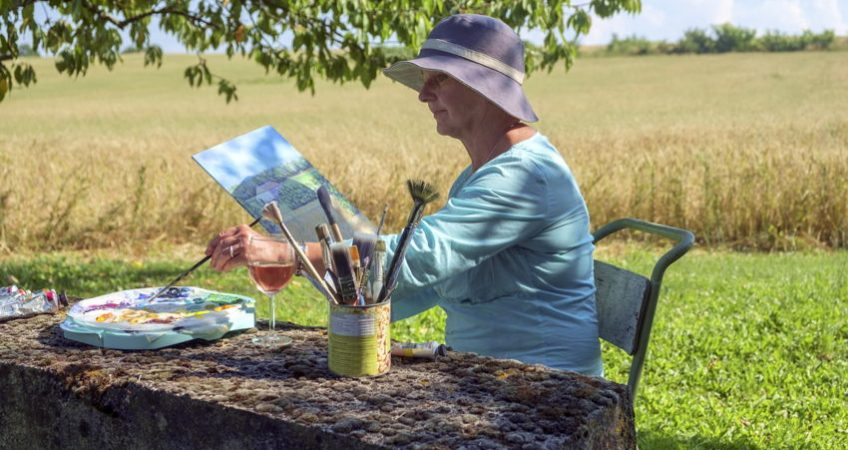 A senior artist in the countryside painting