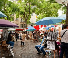 street scene in montemarte paris. artists painting customers who are sheltering under umbrellas underneath spring trees