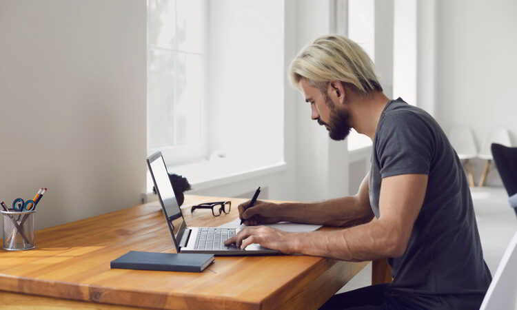 Young guy writing down main points from online business conference
