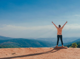 Person stands on top of a mountain celebrating