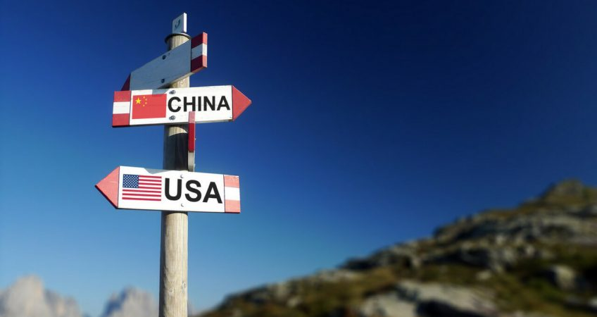 USA and Chinese flags on mountain signpost