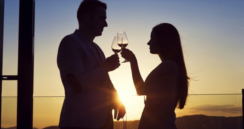 silhouette of 2 people drinking wine in contrast with the sun