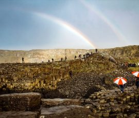 people at giants causeway and rainbows
