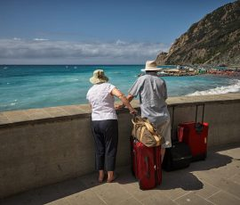 Older travellers with suit cases looking out to sea