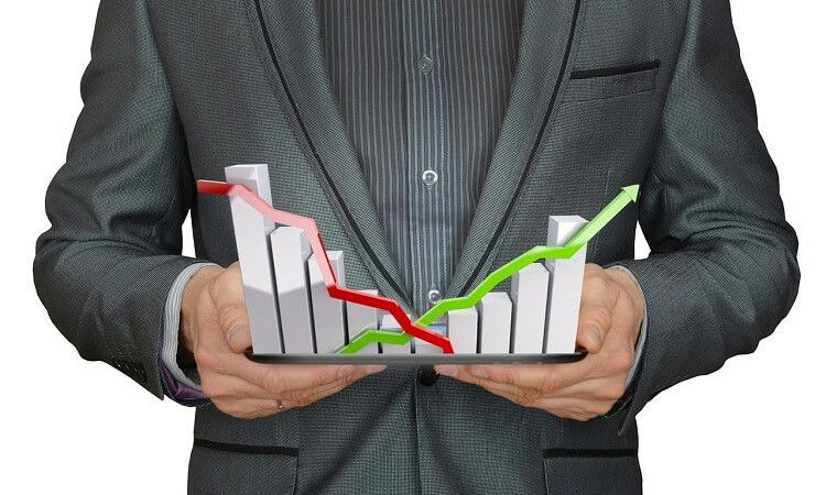 A man in a suit holding graphs