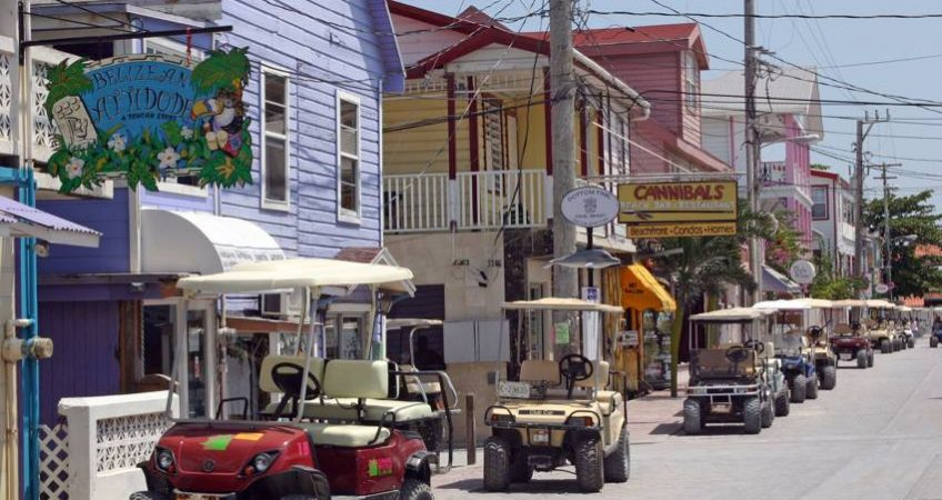 Golf carts parked in line on th eside of the rode with colorful houses on the side in a street on ambergris caye, belize