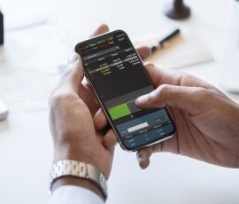 hands of a man holding a smartphone and looking at stocks