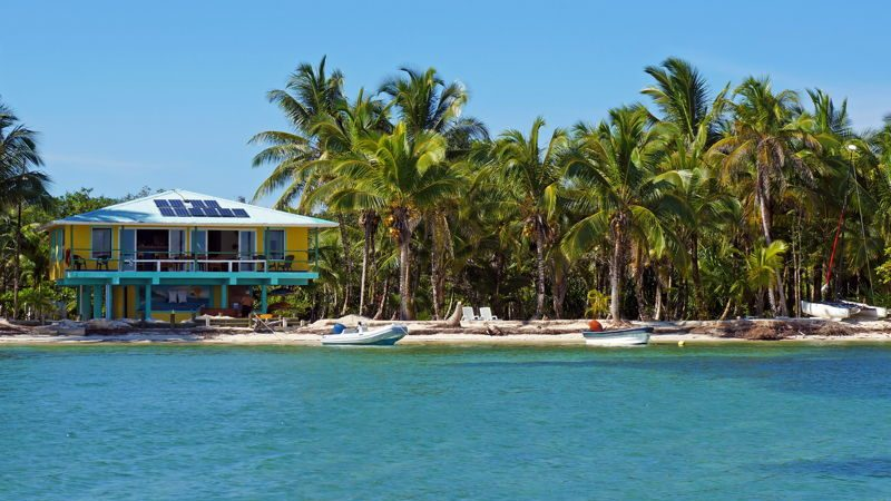 Caribbean property, a colorful house in the beachfront with clear water, white sand and palm trees