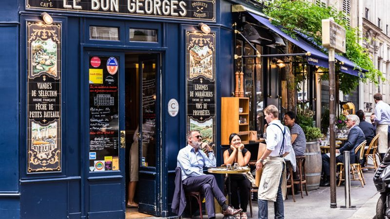 A blue Paris cafe with people sitting on outside tables