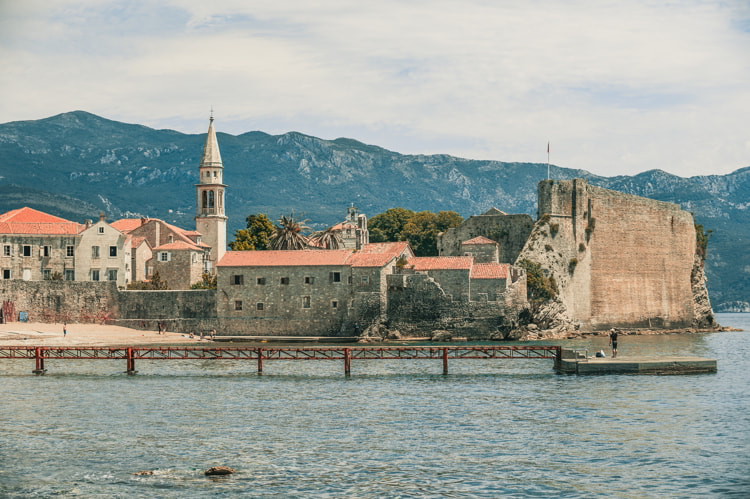 Old town of Budva with churches near ocean and mounts