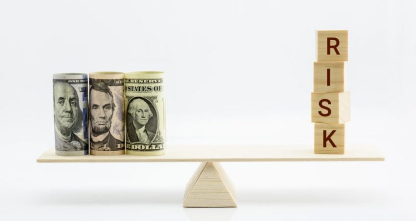 Money balanced on a scale opposite bricks that read risk