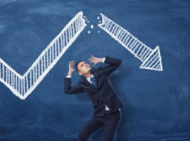 A businessman underneath a falling arrow on finance chart