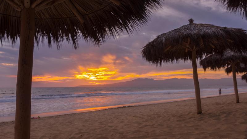 Palapas and people on the beach at sunset at Marival Resort, Nuevo Vallarta, Riviera Nayarit, Mexico.