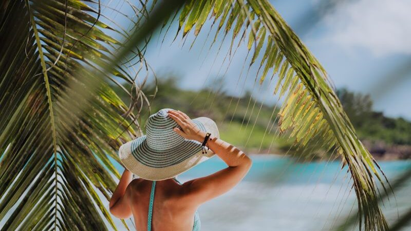 Woman on the beach in the palm trees shadow wearing blue hat.