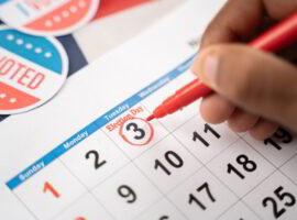 Close up of Hands marking November 3 election day on Calendar as reminder for voting.