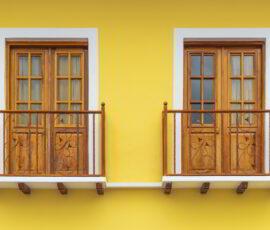 Two colonial style lemon yellow balconies in Cuenca, Ecuador.