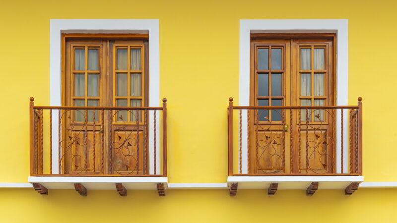 Two colonial style lemon yellow balconies in Cuenca, Ecuador.