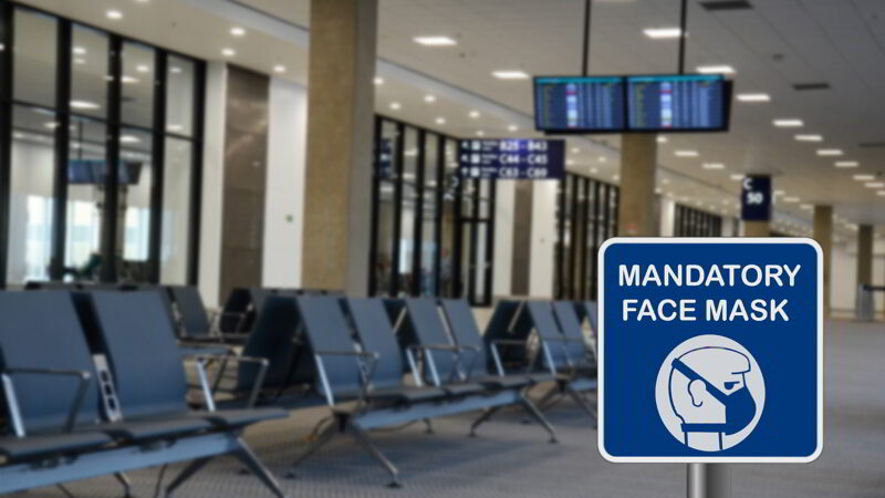Blue sign warning of that face mask is mandatory due to Covid-19 or coronavirus in airport.