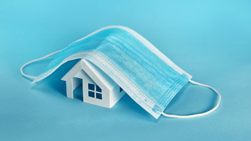 Paper house model cover by a mask isolated on blue background.