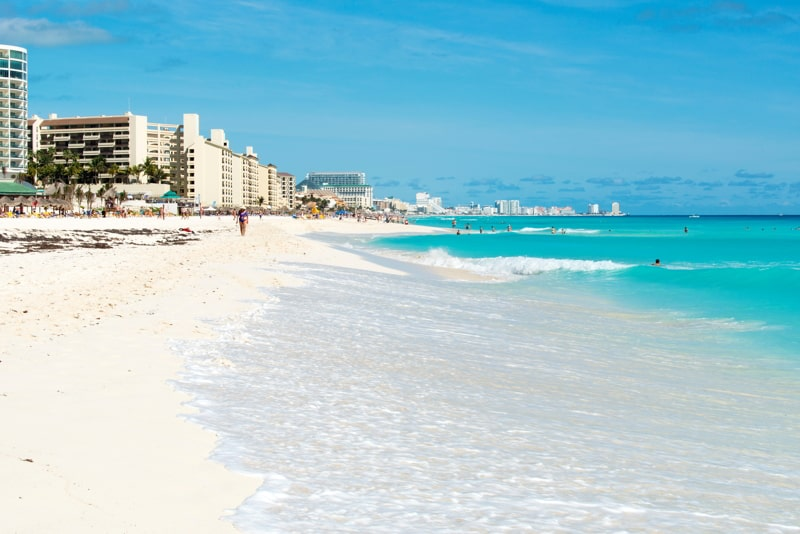 Tourists enjoy the sunny weather and relaxing on the beautiful beach in Cancun, Mexico.