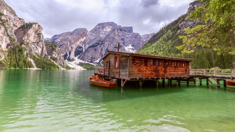 View of a boat house on the famous Lake Braies with emerald water in Italy