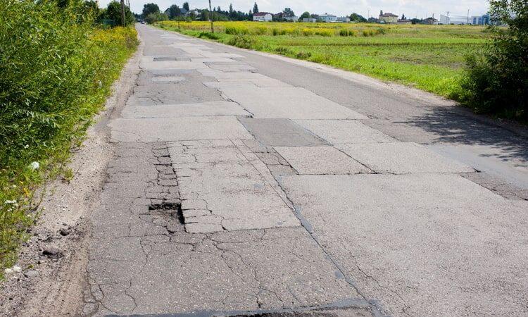 Many chuckholes in asphalt damaged road.